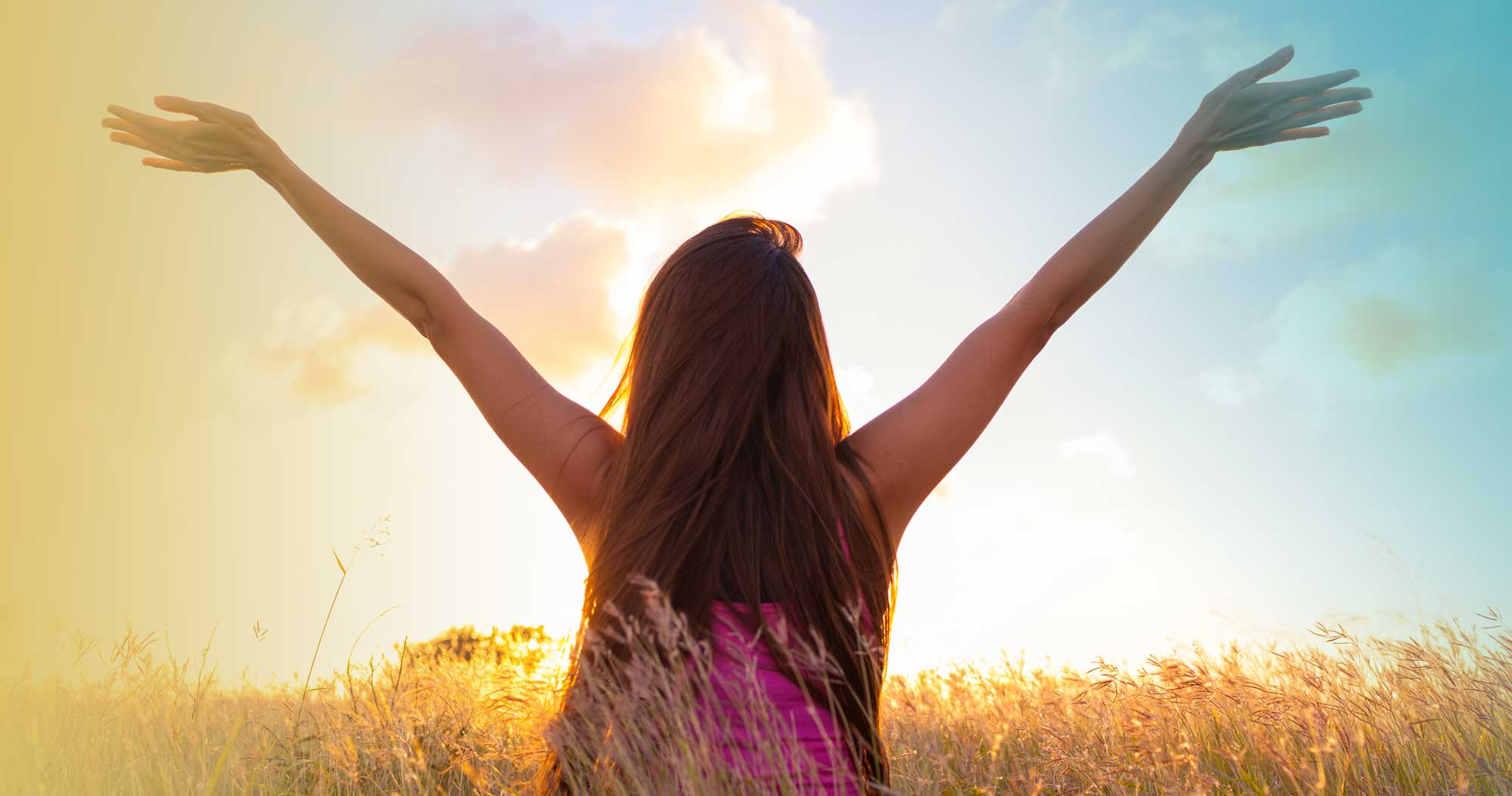 Woman with outstretched arms in corn field