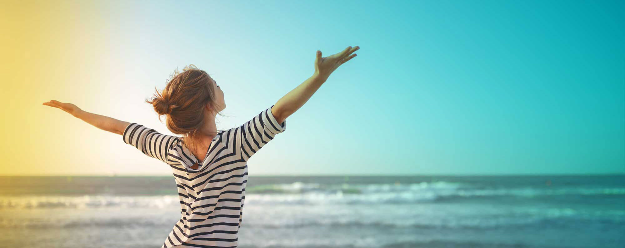 Woman with arms outstretched on beach